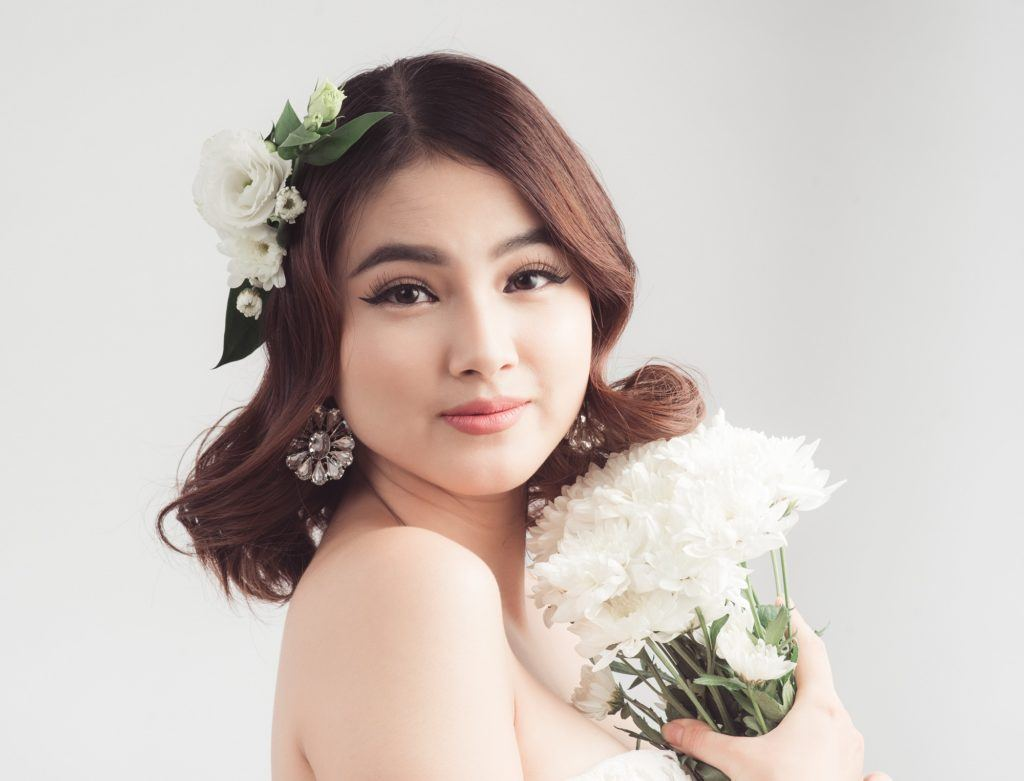 Wedding hairstyles for medium hair: Closeup shot of a bride with shoulder-length wavy brown hair with floral hair piece holding a white bouquet standing against a light gray background