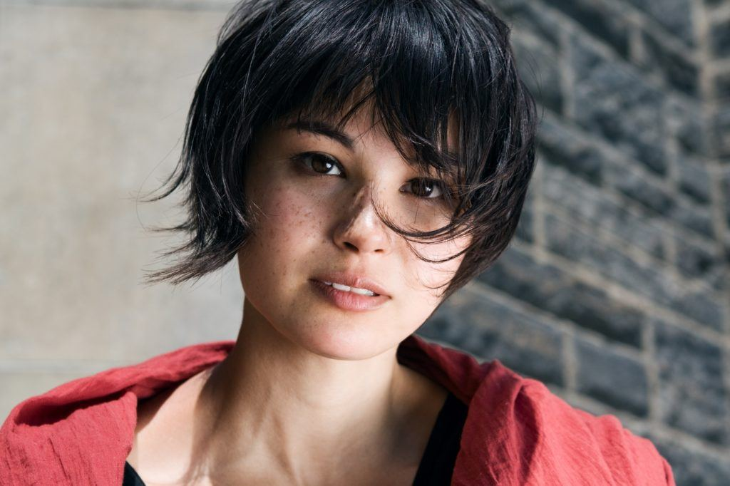 WIspy hair: Closeup shot in an outdoor location of a girl wearing a red jacket with short black wispy hair