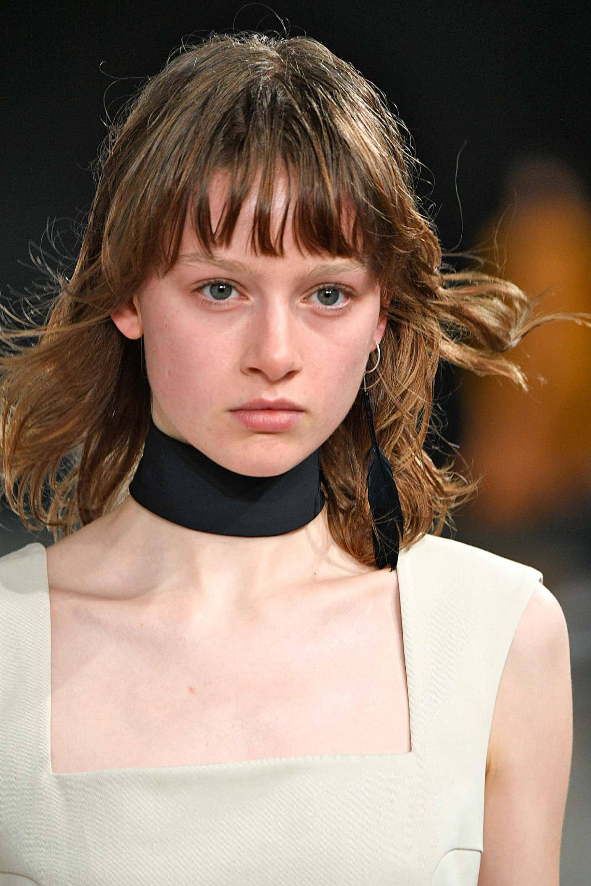 Wispy hair: Closeup shot of woman with wearing white sleeveless blouse and black choker with brown shoulder length wispy hair and bangs