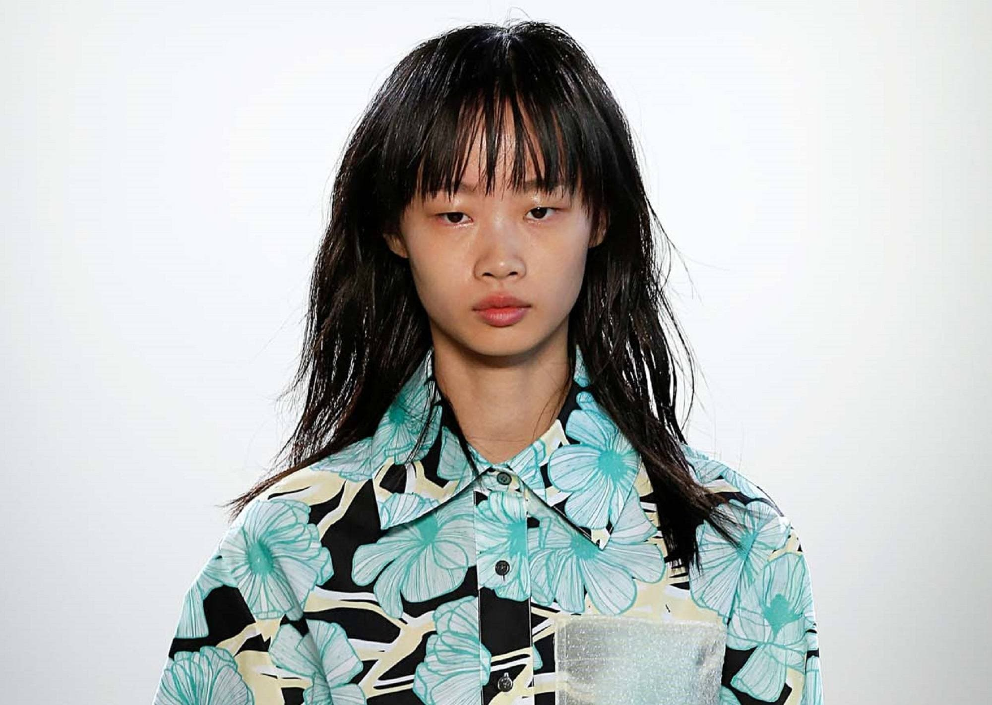 Wispy hair: Closeup shot of Asian woman wearing a printed dress with long black wispy hair and bangs against white background