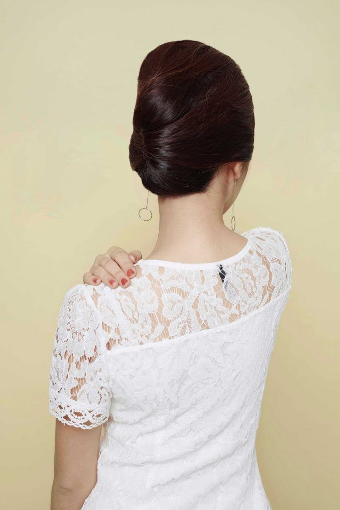 Asian woman with a French twist hairstyle wearing a white dress