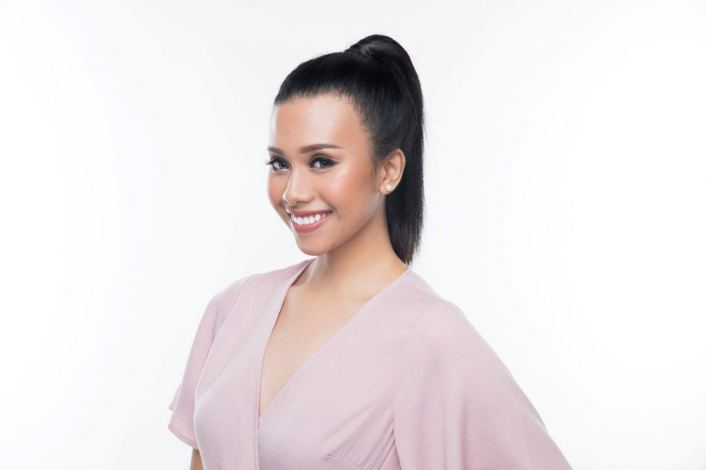 Asian woman with a high ponytail wearing a pink blouse