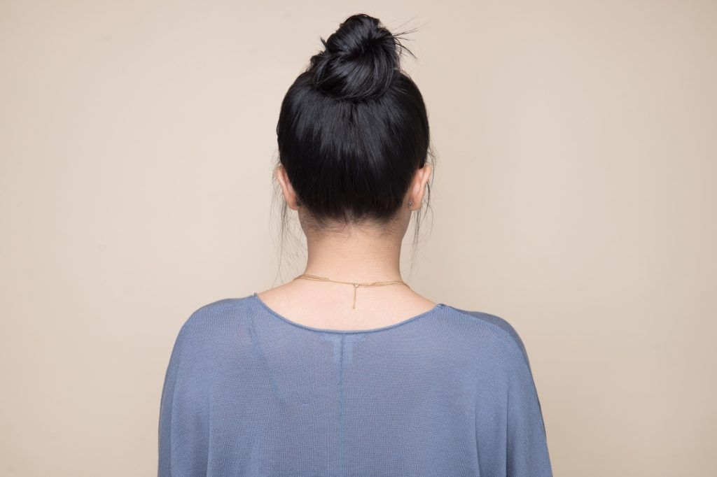 Back shot of an Asian woman with a messy bun hairstyle