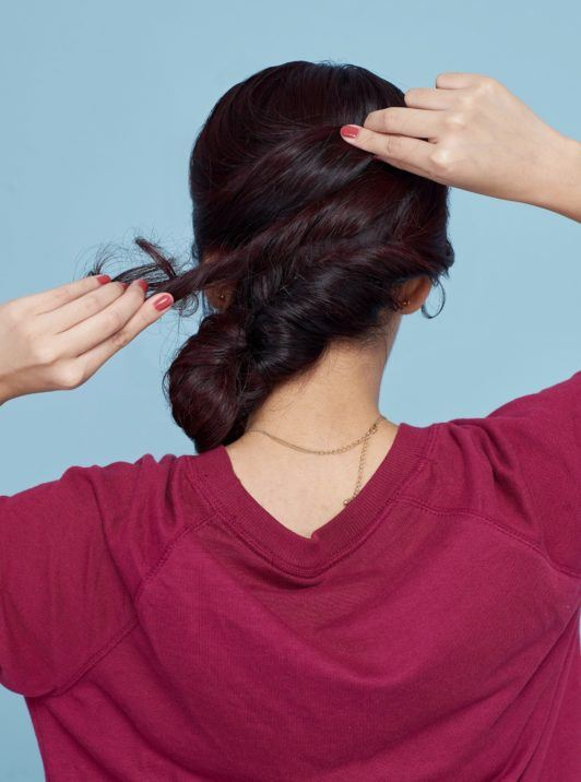 Banana bun: Back shot of Asian woman wearing a red sweater putting her black hair in a banana bun standing against a blue background