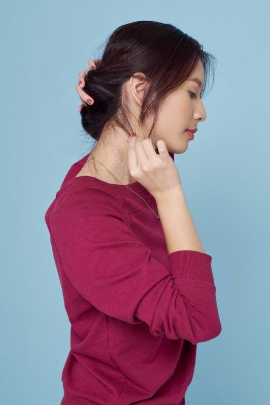 Banana bun: Side view of Asian woman wearing a red sweater styling her hair standing against a blue background