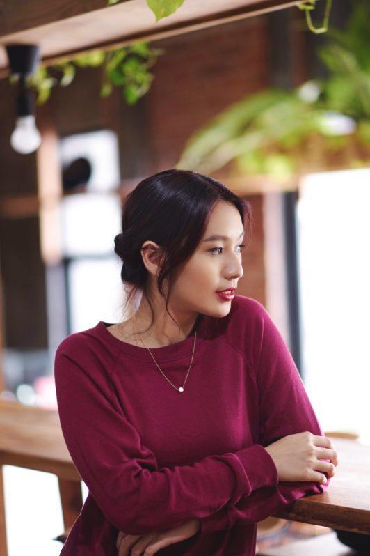 Banana bun: shot of an Asian woman wearing a red sweater with black hair in a banana bun sitting in a cafe