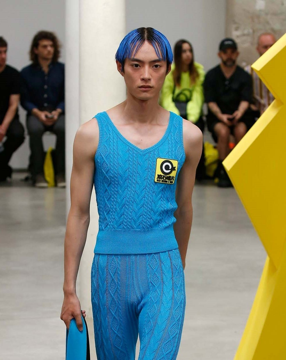 Man with blue hair wearing a blue top and pants walking on the runway