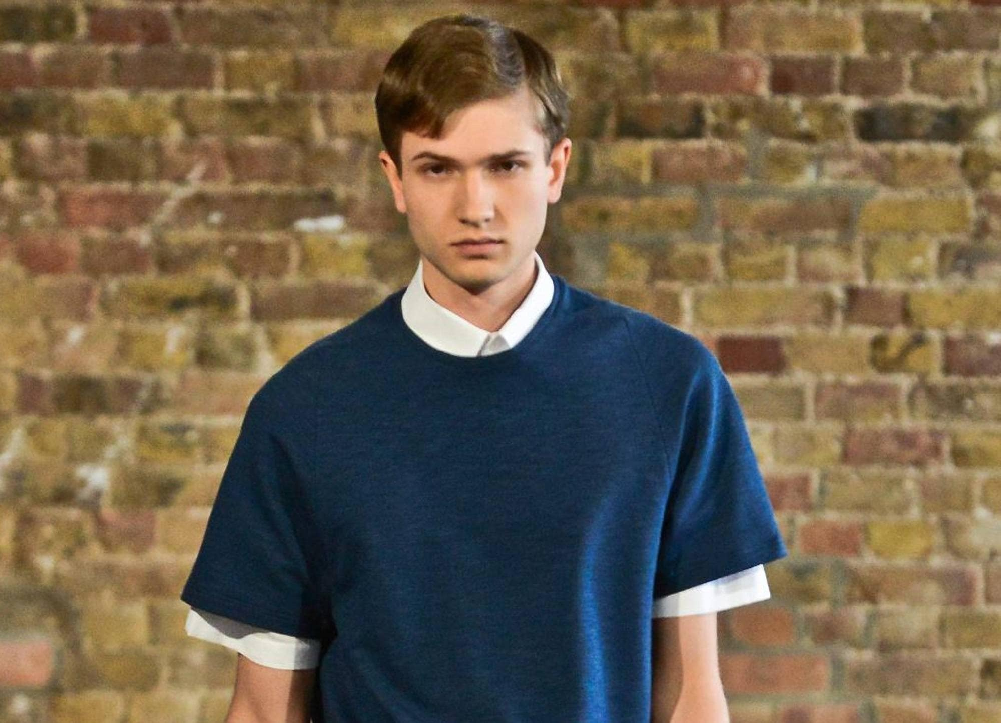 Best hair color for men: Caucasian man with bronde hair wearing a dark blue shirt against a brick wall