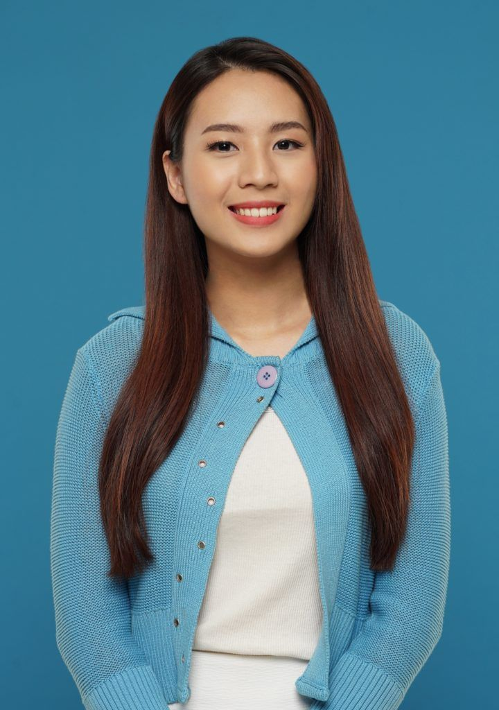 Haircuts for rainy season: Asian woman with long dark brown hair wearing a blue cardigan and white dress against a blue background