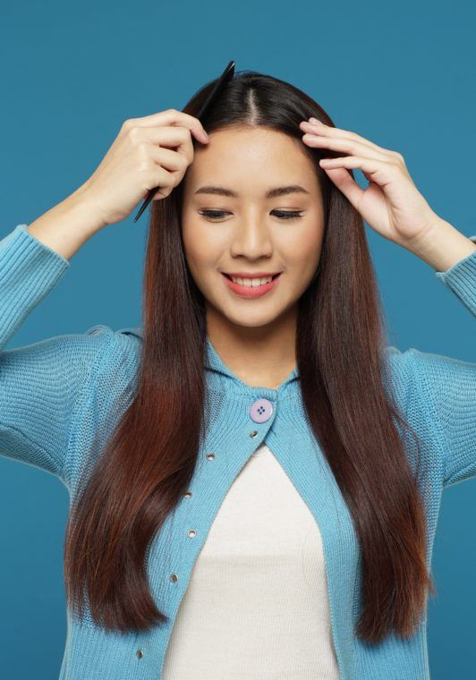 Curly side part hairstyle: Asian woman parting her long dark brown hair against a blue background