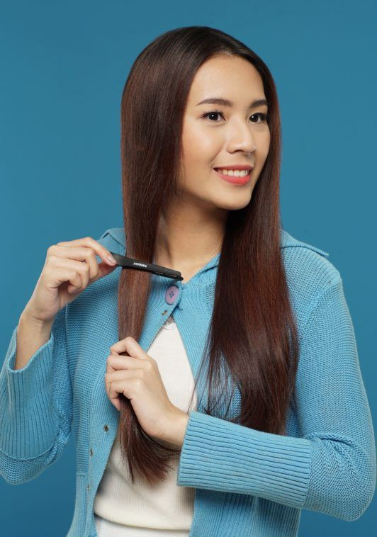 Curly side part hairstyle: Asian woman clipping her long dark brown hair against a blue background