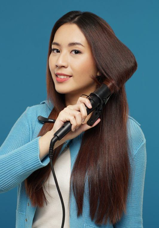 Curly side part hairstyle: Asian woman with long dark brown hair curling her hair against a blue background