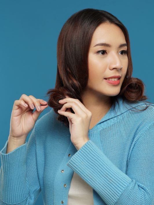 Curly side part hairstyle: Asian woman pinning curls in her long brown hair against a blue background