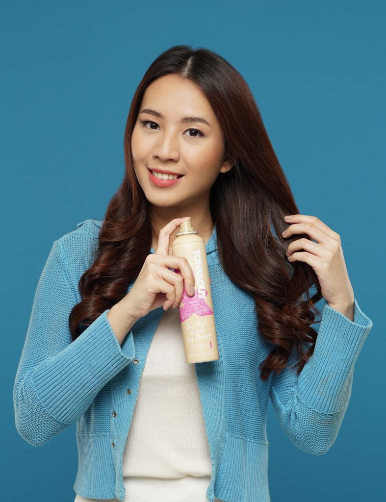 Curly side part hairstyle: Asian woman spraying dry shampoo on her long dark brown hair against a blue background