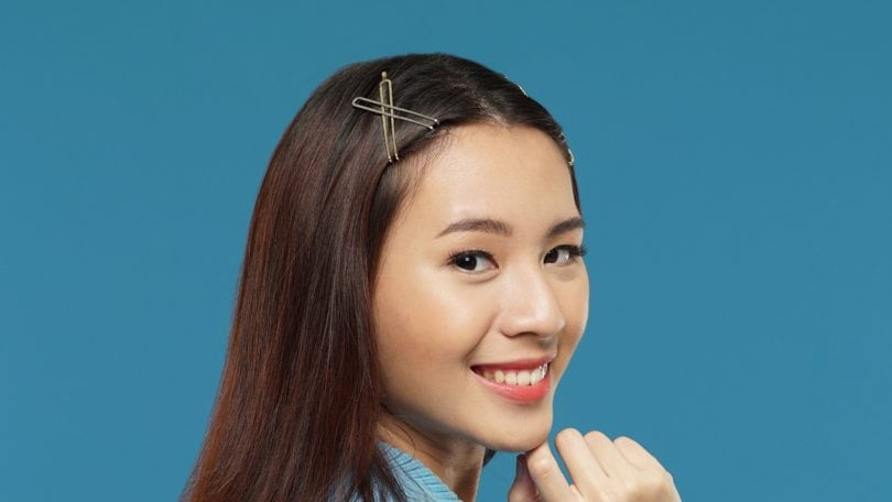 Curly side part hairstyle Asian woman with long dark brown hair with hair clips wearing a blue cardigan against a blue background