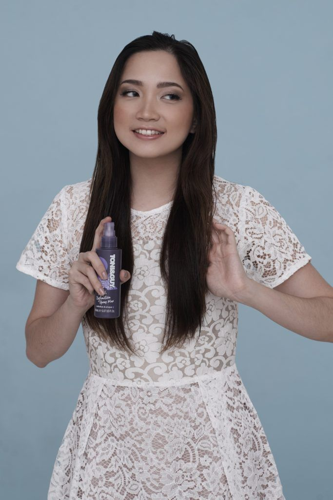 Curly side ponytail: Asian woman wearing white dress spraying wax on long black hair standing against a blue background