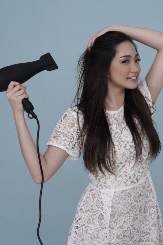 Curly side ponytail: Asian woman wearing white dress blow drying her long black hair