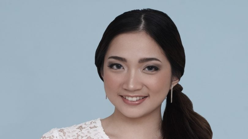Curly side ponytail: Closeup shot of Asian woman wearing white dress with curly side ponytail against a blue background