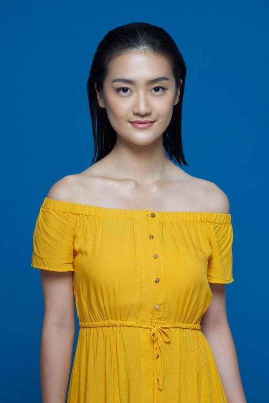 Flipped-out short bob: Asian woman with short black hair wearing a yellow dress against a blue background