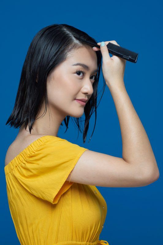 Flipped-out short bob: Asian woman parting her short black hair using a tail comb against a blue background
