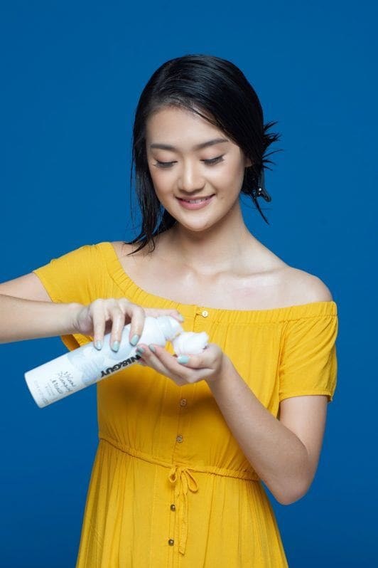 Flipped-out short bob: Asian woman with short black hair wearing a yellow dress pouring hair mousse on her hand