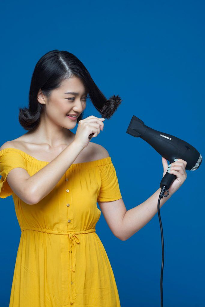 Flipped-out short bob: Asian woman blow drying her short black hair against a blue background