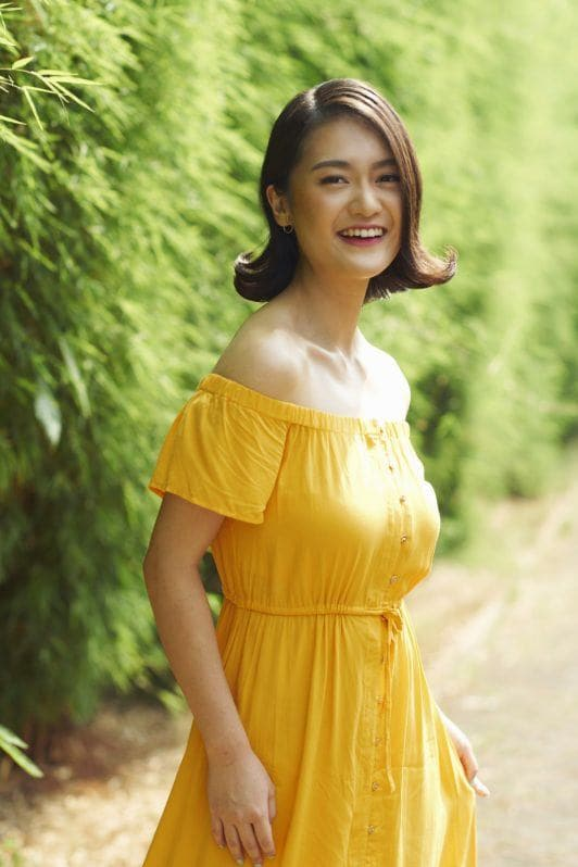 Flipped-out short bob: Asian woman with short black hair wearing a yellow dress outdoors