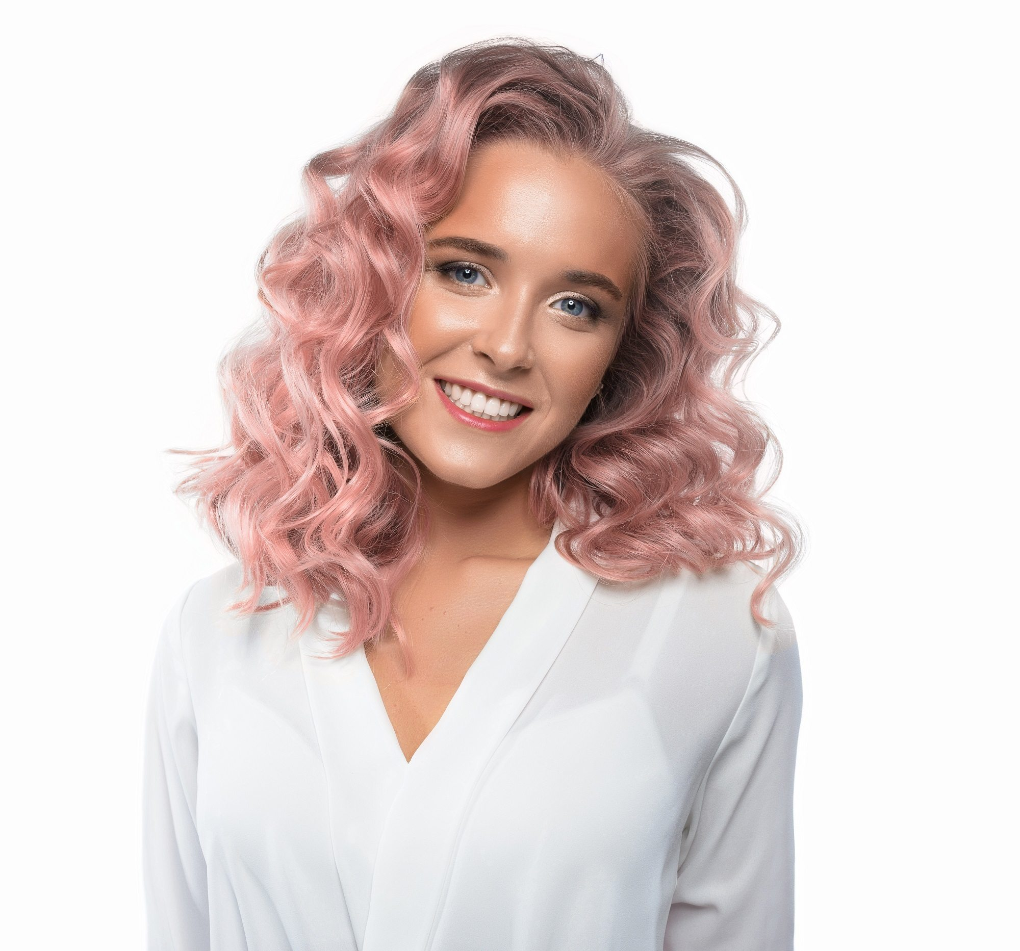 Hair color for curly hair: Closeup shot of a woman with pink shoulder-length curly hair wearing white top against white background