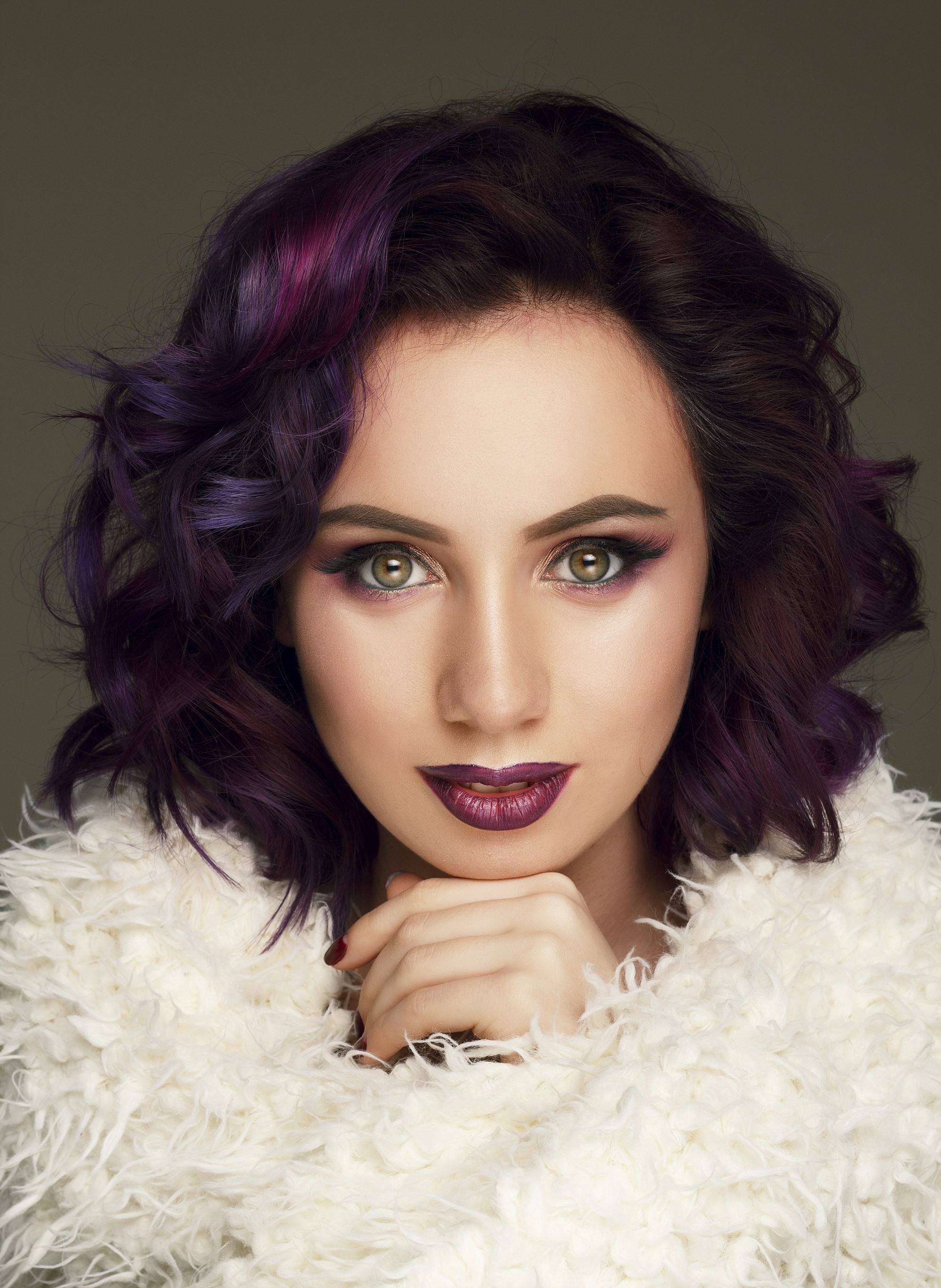Hair color for curly hair: Closeup shot of a woman wearing white fur coat with short purple curly hair
