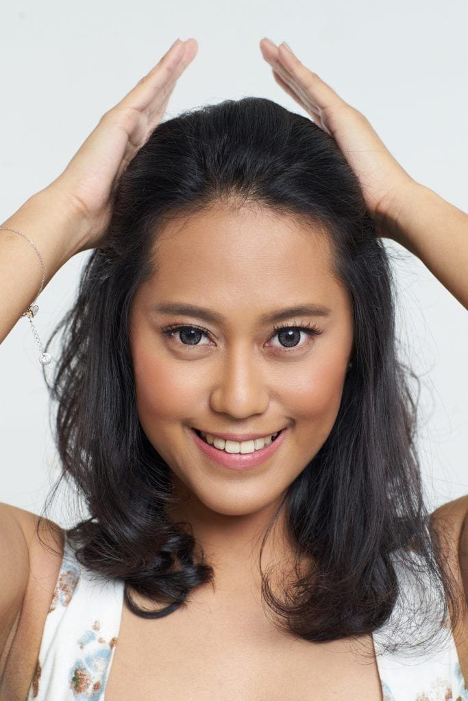 Half ponytail: Closeup shot of an Asian woman gathering a section of hair on top of her head