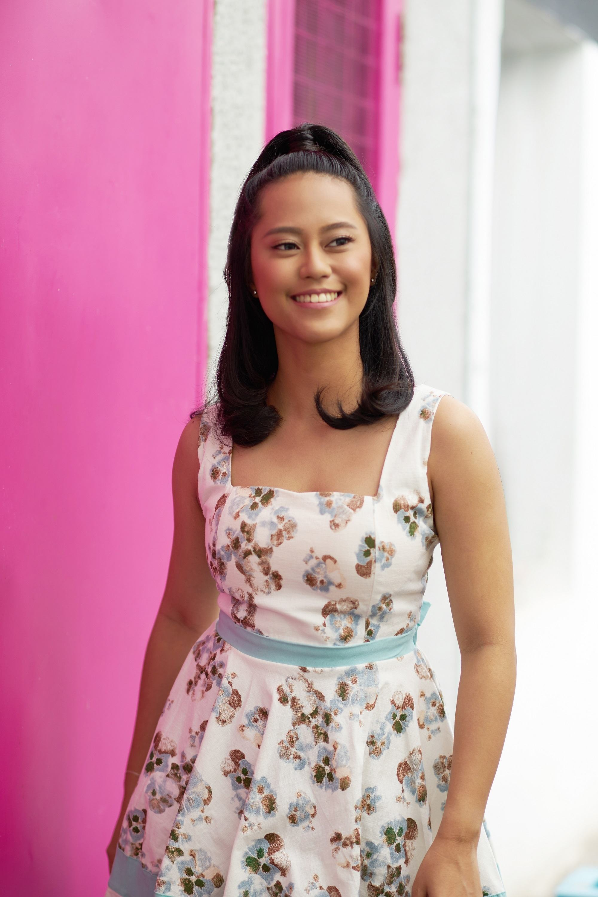 Half ponytail: Asian woman with shoulder-length black hair in a half ponytail wearing a floral dress against a pink and white wall