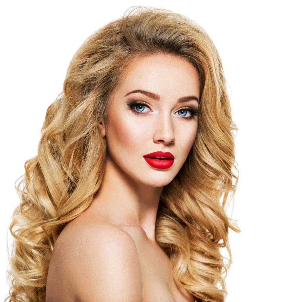 Honey blonde: Closeup shot of a woman with long blonde wavy hair and red lips against a white background