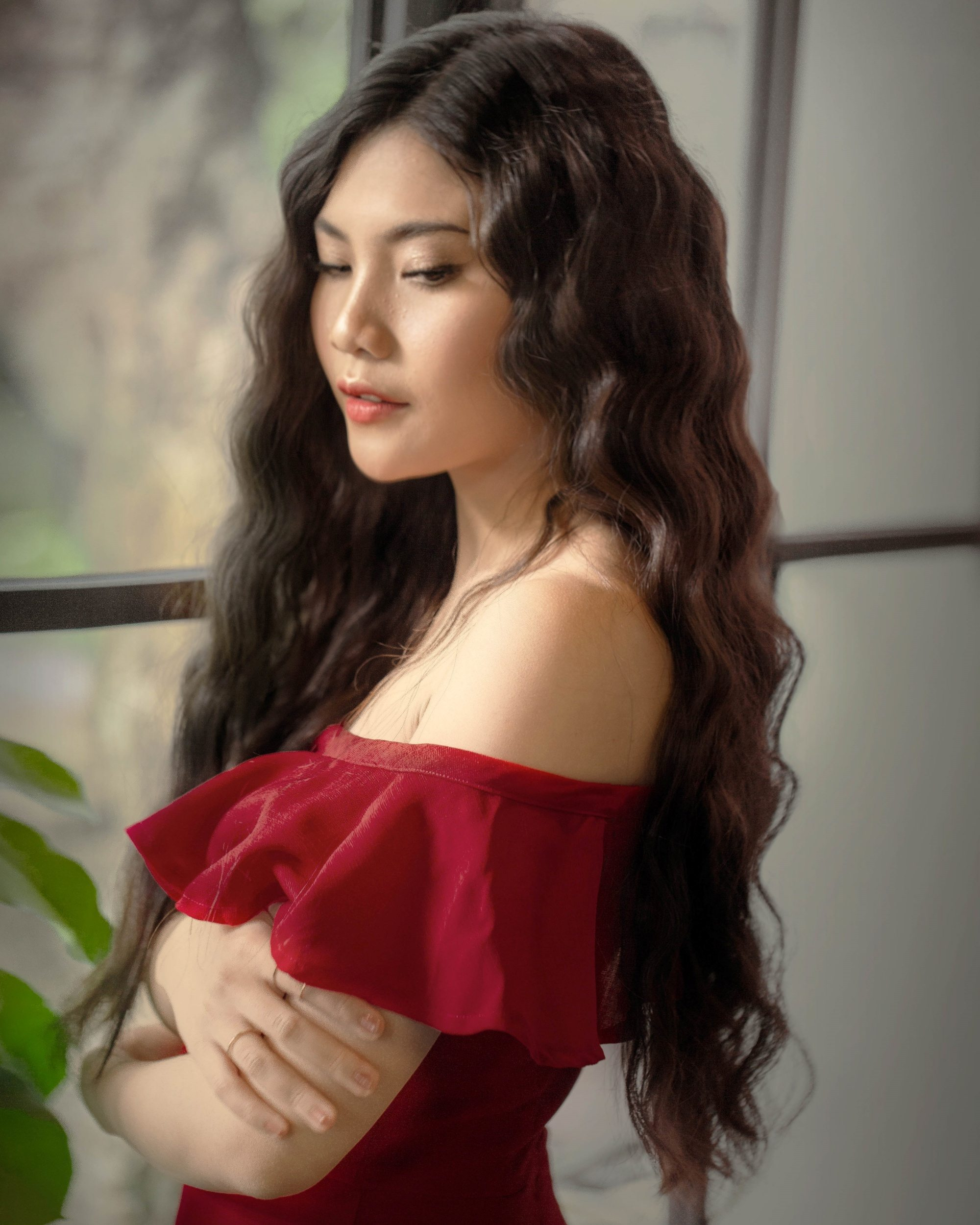 Asian woman with long black asteria hair wearing an off-shoulder red dress