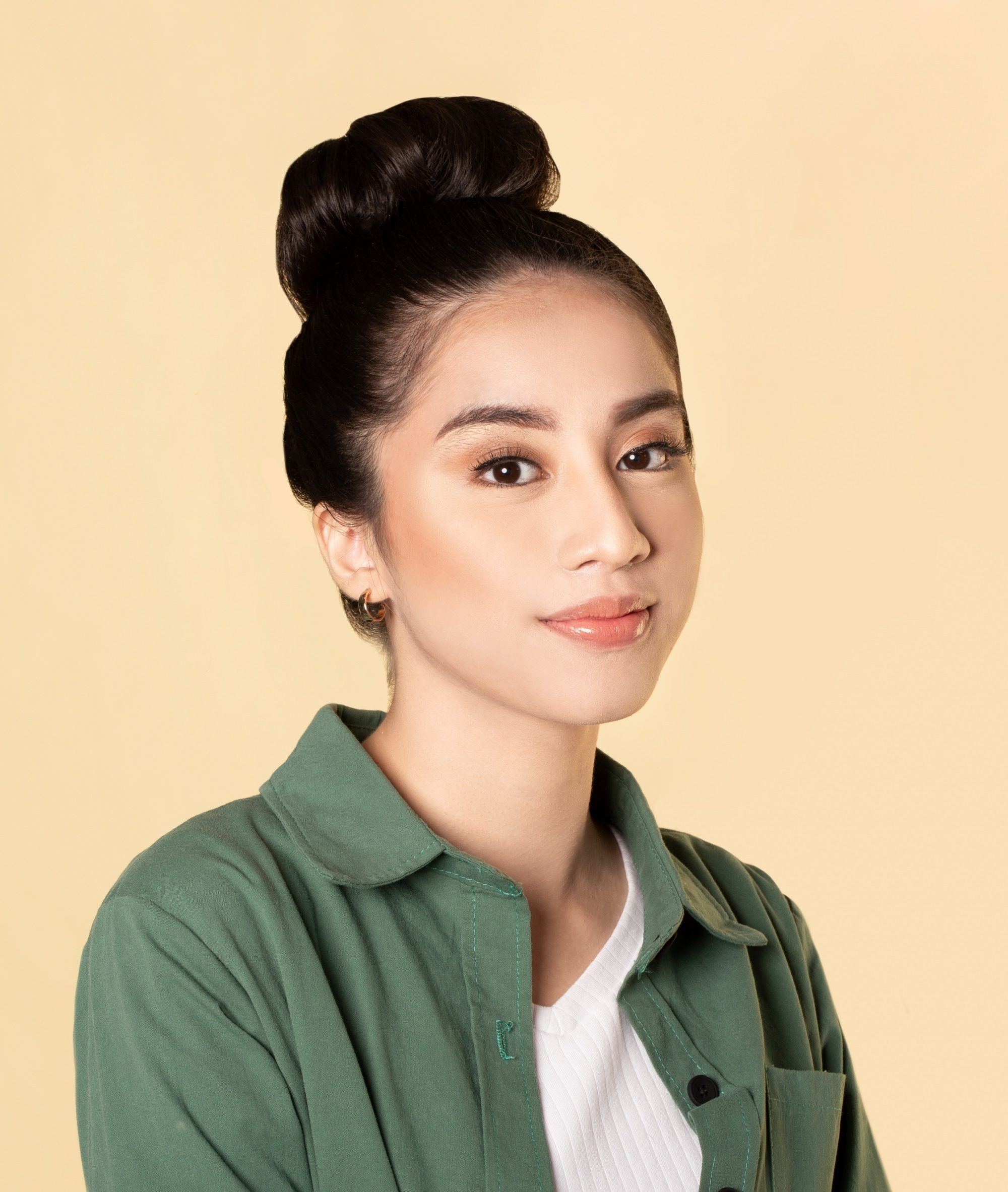Asian woman with long black hair in a big top knot hairstyle