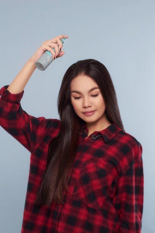 Messy ponytail: Asian woman wearing plaid blouse spraying sea salt spray on her long black hair standing against a blue background