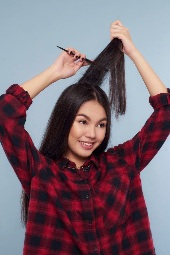Messy ponytail: Asian woman wearing plaid shirt teasing her long black hair standing against a blue background