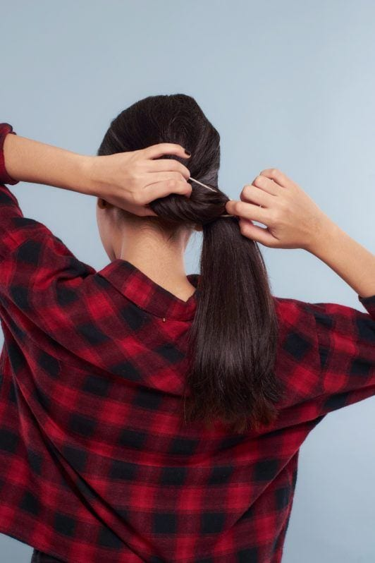Messy ponytail: Back shot of Asian woman wearing plaid blouse tying her long black hair and standing against a blue background