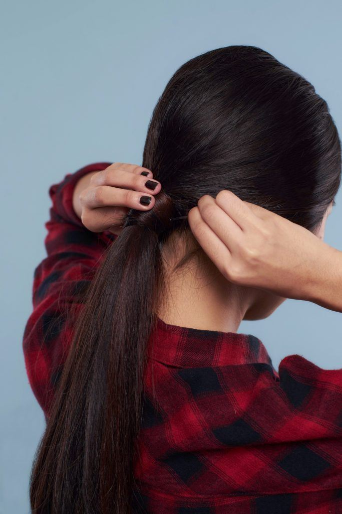 Messy ponytail: Back shot of Asian woman wearing plaid blouse putting her long black hair in ponytail standing against a blue background