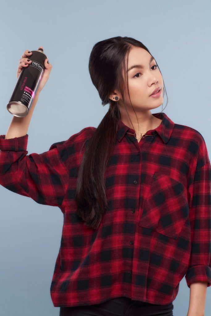 Messy ponytail: Asian woman wearing plaid blouse spritzing hairspray on long black hair and standing against a blue background