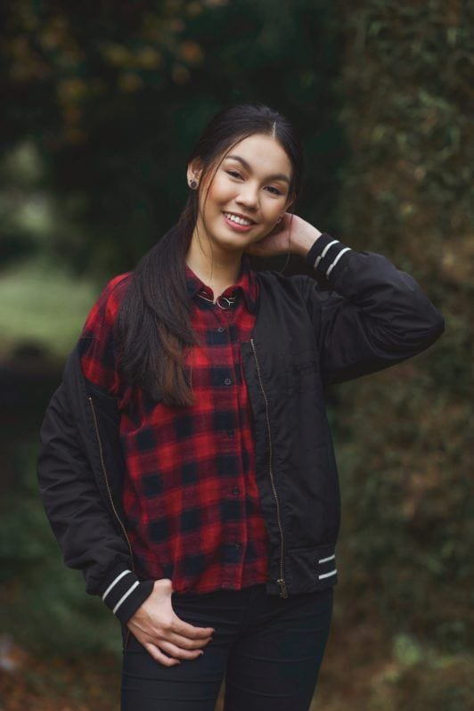 Messy ponytail: Asian woman wearing plaid blouse and dark blue jacket with long black hair in ponytail standing in a park