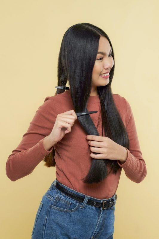 Nine strand braid: Asian woman wearing a brown long-sleeved shirt clipping her long black hair