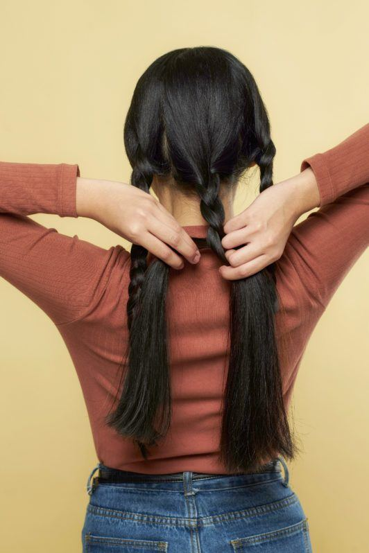 Nine strand hair: Back shot of Asian woman wearing brown long-sleeved shirt braiding her long black hair