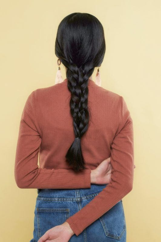 Nine strand braid: Back shot of Asian woman wearing long-sleeved shirt with long black hair in nine strand braid
