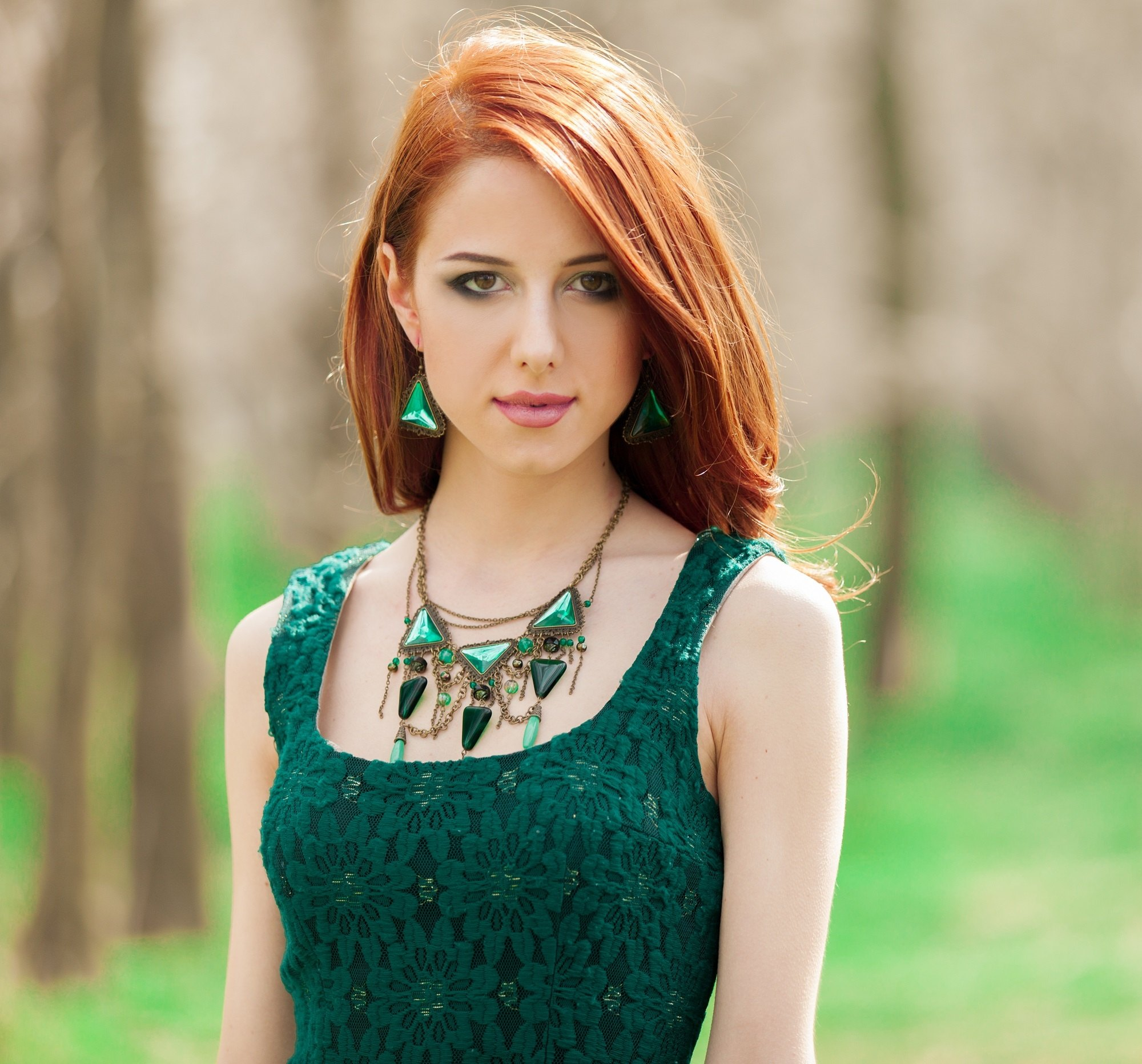 Orange hair: Woman with long red orange hair wearing a green sleeveless dress outdoors
