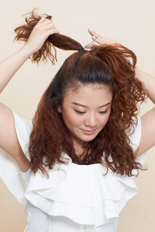 Pull through braid: Asian woman wearing white blouse tying her brown curly hair and standing against an oyster-colored background