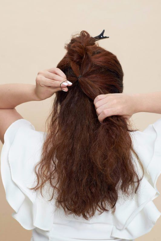 Pull through braid: Back shot of Asian woman wearing white blouse styling her curly hair and standing against an oyster-colored background
