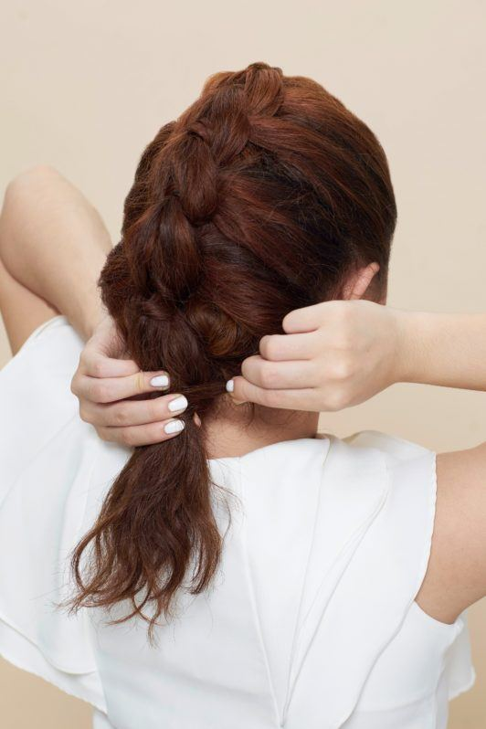 Pull through braid: Back shot of Asian woman wearing white blouse styling her brown curly hair
