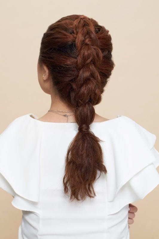 Pull through braid: Back shot of Asian woman wearing a white blouse with curly hair in pull through braid