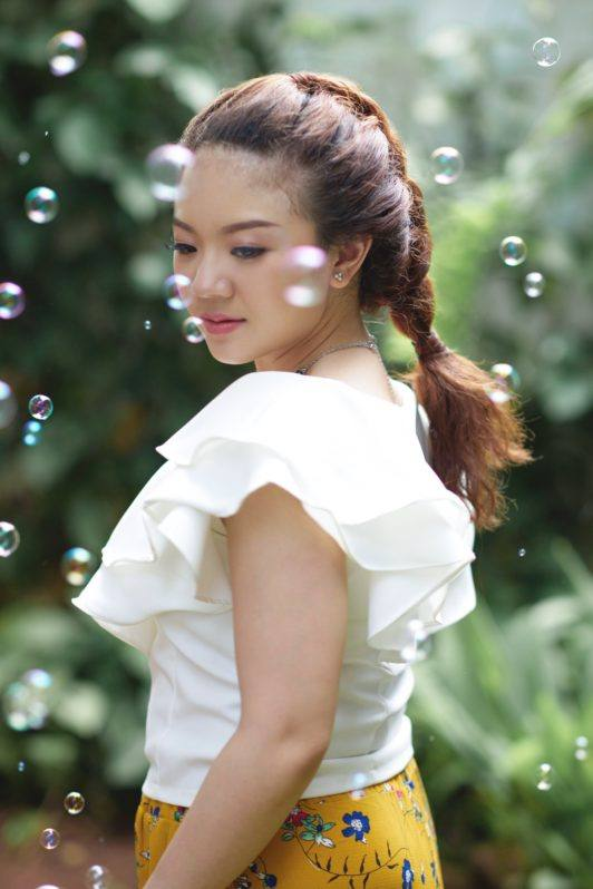 Pull through braid: Asian woman wearing white blouse with curly hair in pull through braid standing in a park