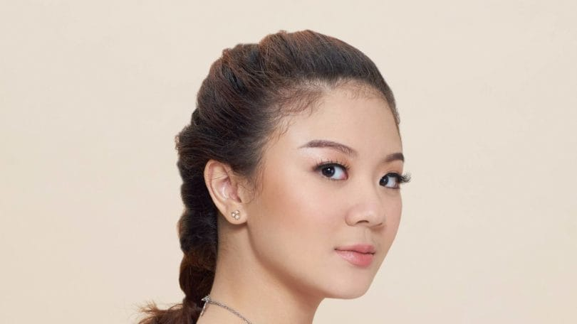 Pull through braid: Closeup shot of Asian woman wearing white blouse with brown hair in pull through braid standing against oyster-colored background